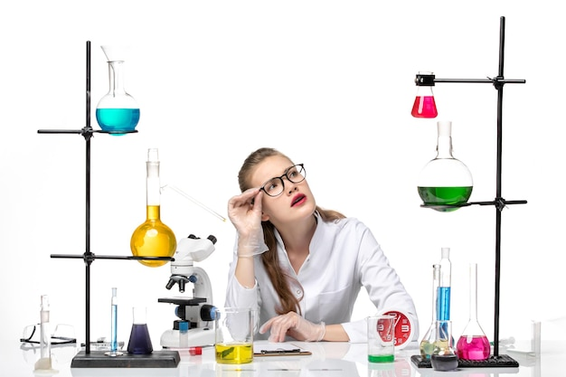 Vooraanzicht vrouwelijke arts in wit medisch pak zit tafel met oplossingen op een witte achtergrond virus gezondheid covid pandemie chemie