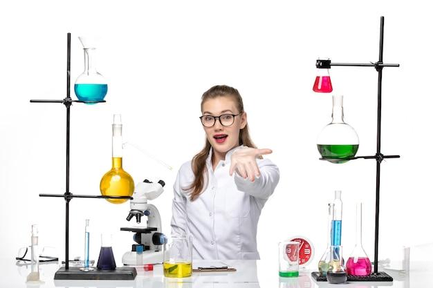 Vooraanzicht vrouwelijke arts in wit medisch pak zit tafel met oplossingen op lichte witte achtergrond virus covid pandemie chemie