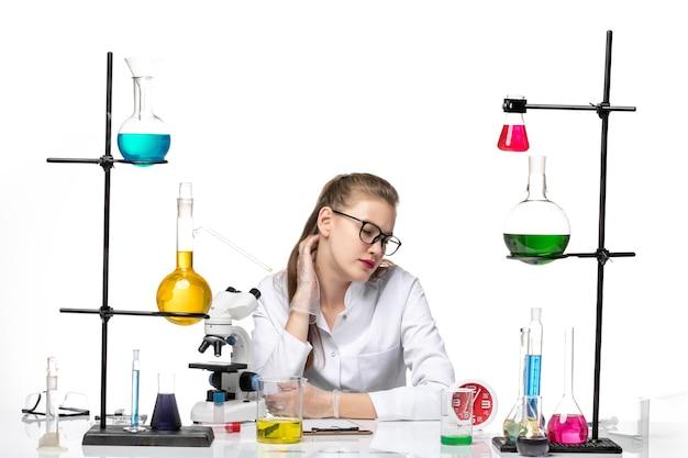 Vooraanzicht vrouwelijke arts in wit medisch pak zit tafel met oplossingen op wit bureau covid pandemisch chemievirus