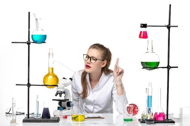 Vooraanzicht vrouwelijke arts in wit medisch pak zit tafel met oplossingen op wit bureau virus covid pandemie chemie