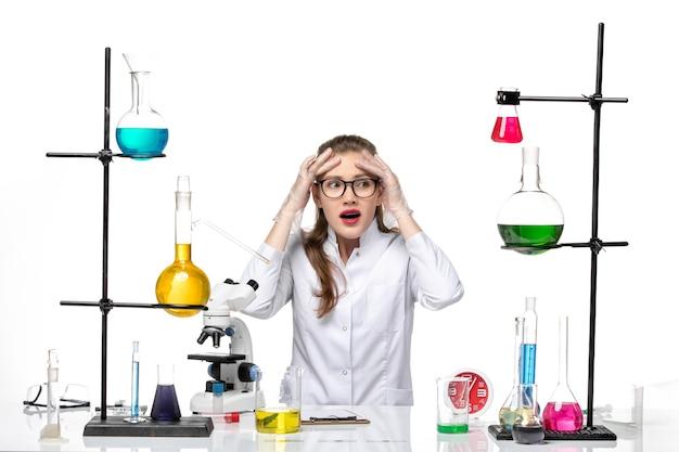 Vooraanzicht vrouwelijke arts in wit medisch pak zit tafel met oplossingen op witte vloer virus gezondheid covid pandemie chemie