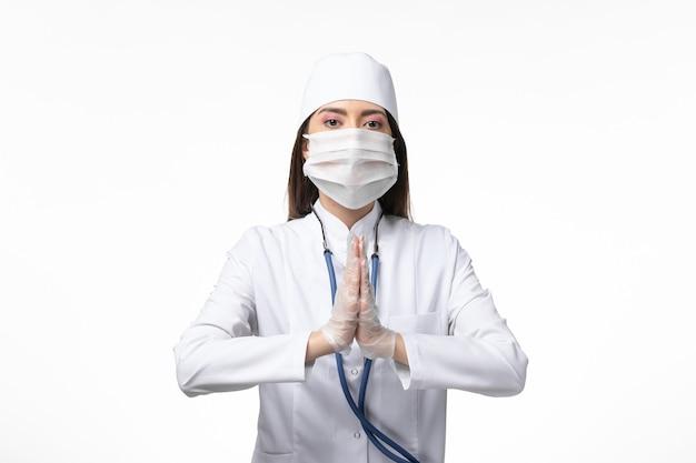 Vooraanzicht vrouwelijke arts in wit steriel medisch pak met masker vanwege coronavirus bidden op witte muur ziekte covid- pandemische virusziekte