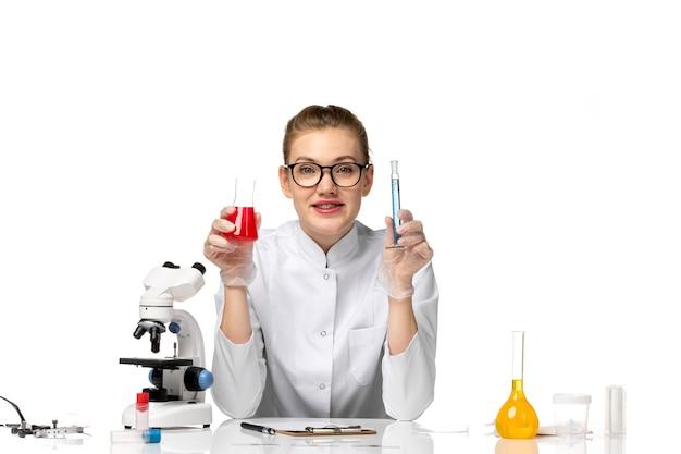 Vooraanzicht vrouwelijke arts in witte medische pak werken met oplossingen op witte ruimte