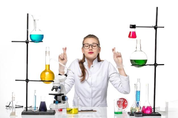 Vooraanzicht vrouwelijke arts in witte medische pak zit tafel met oplossingen op witte achtergrond covid chemie pandemie