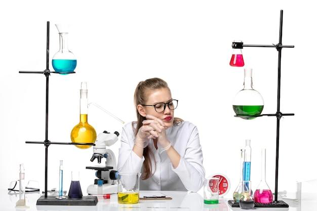 Vooraanzicht vrouwelijke arts in witte medische pak zit tafel met oplossingen op witte achtergrond covid pandemische chemie virus