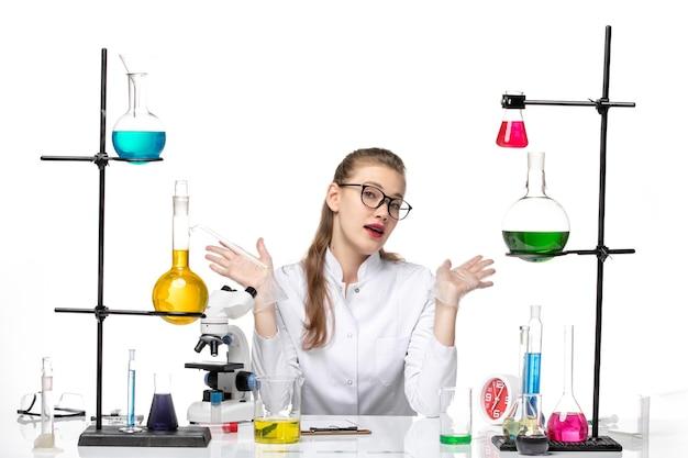 Vooraanzicht vrouwelijke arts in witte medische pak zittend met oplossingen op wit bureau virus chemie pandemie covid