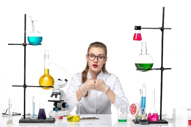 Vooraanzicht vrouwelijke arts in witte medische pak zittend met oplossingen op witte achtergrond virus chemie pandemie covid