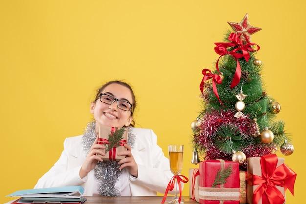 Vooraanzicht vrouwelijke arts kerstcadeau te houden