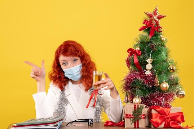 Vooraanzicht vrouwelijke arts kerstmis vieren met een glas champagne