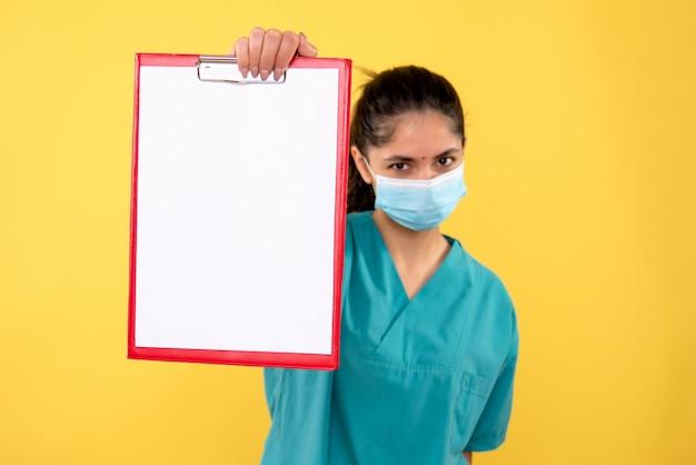 Vooraanzicht vrouwelijke arts klembord houden in haar hand staan