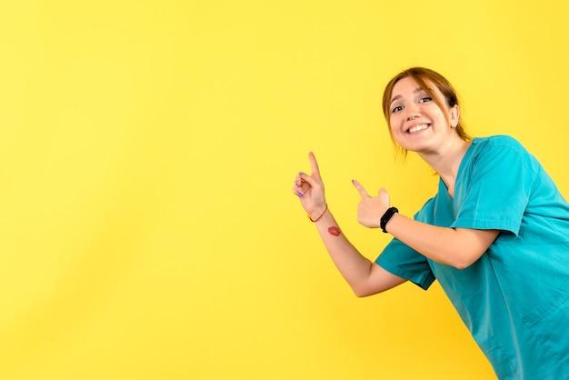 Vooraanzicht vrouwelijke arts lachend op gele ruimte