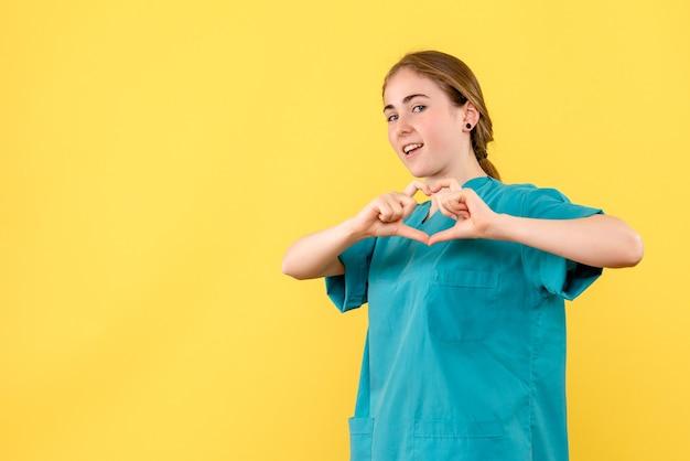 Vooraanzicht vrouwelijke arts liefde verzenden op gele achtergrond medic gezondheid ziekenhuis virus emotie