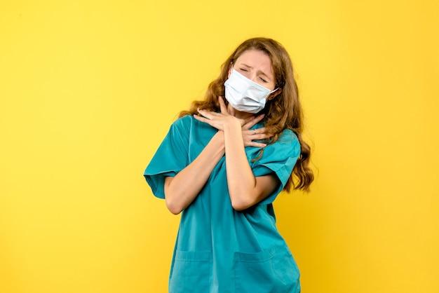 Vooraanzicht vrouwelijke arts met ademhalingsproblemen op gele ruimte