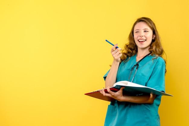 Vooraanzicht vrouwelijke arts met analyses op gele ruimte