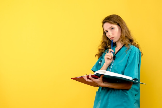 Vooraanzicht vrouwelijke arts met analyses op gele vloer emotie ziekenhuis gezondheid medic