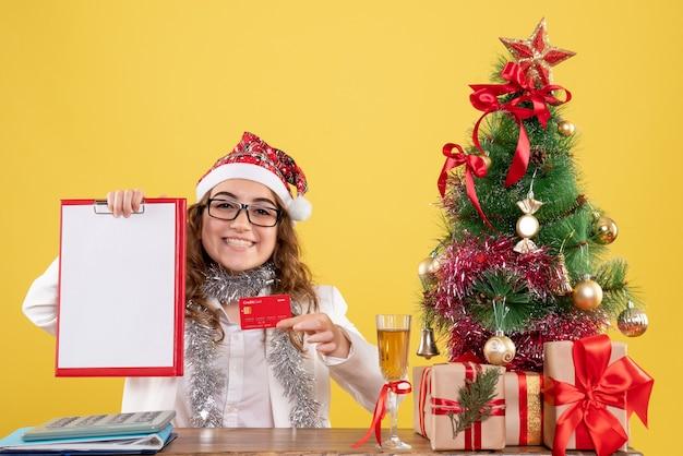 Vooraanzicht vrouwelijke arts met bankkaart en dossiernota