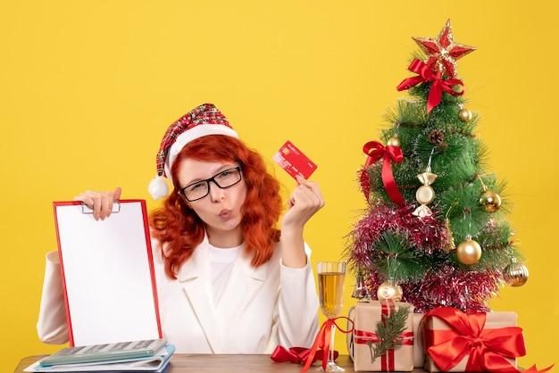 Vooraanzicht vrouwelijke arts met bankkaart en nota