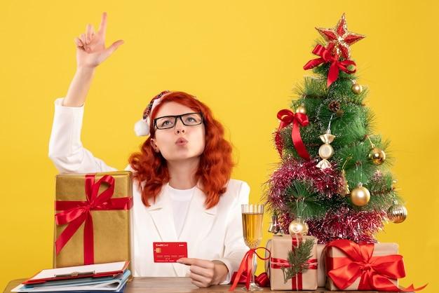 Vooraanzicht vrouwelijke arts met bankkaart rond kerstcadeautjes en boom