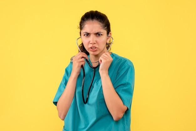 Vooraanzicht vrouwelijke arts met behulp van stethoscoop staan