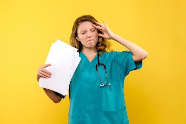 Vooraanzicht vrouwelijke arts met bestanden benadrukt op gele ruimte