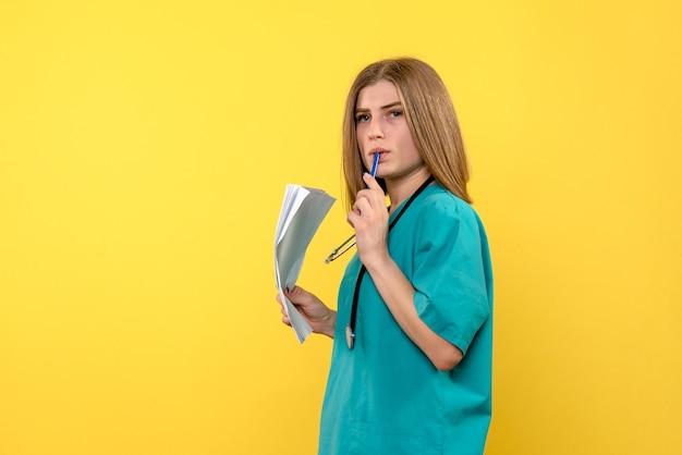 Vooraanzicht vrouwelijke arts met bestanden op gele ruimte
