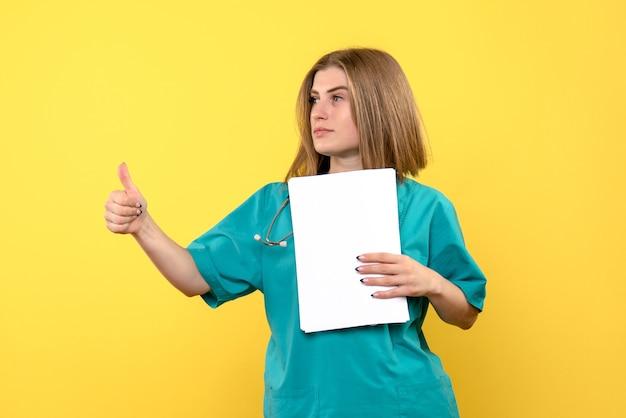 Vooraanzicht vrouwelijke arts met bestanden op gele vloer ziekte medisch ziekenhuis
