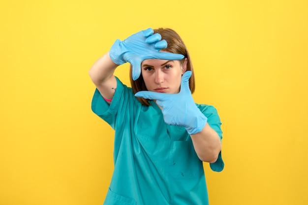 Vooraanzicht vrouwelijke arts met blauwe handschoenen op gele ruimte
