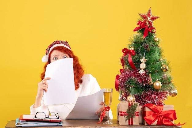 Vooraanzicht vrouwelijke arts met documenten achter tafel met cadeautjes