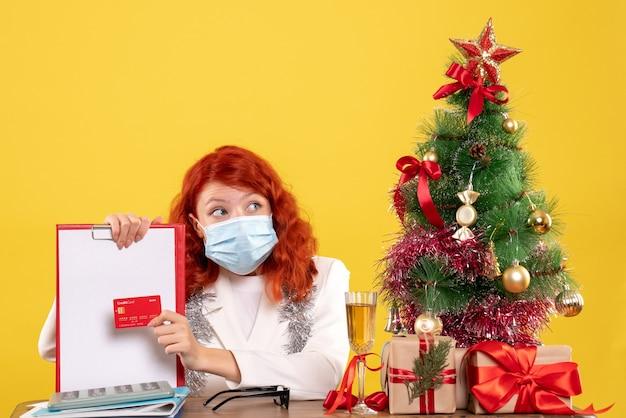 Vooraanzicht vrouwelijke arts met dossiernota en bankkaart