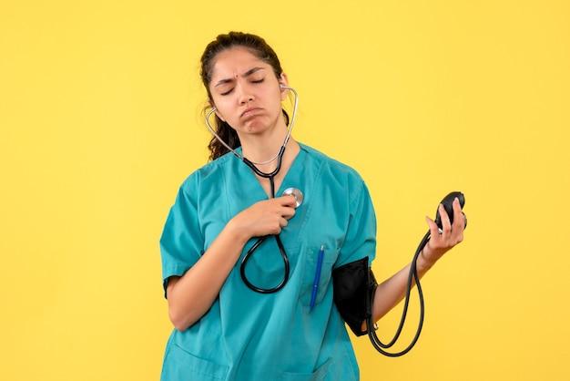 Vooraanzicht vrouwelijke arts met gesloten ogen die bloeddrukmeters staande houdt