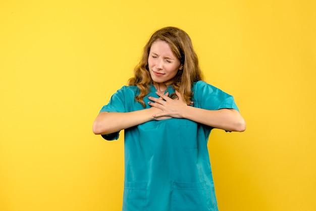 Vooraanzicht vrouwelijke arts met hartzeer op gele ruimte