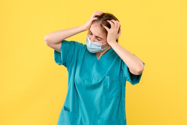 Vooraanzicht vrouwelijke arts met hoofdpijn op gele achtergrond covid-ziekenhuis gezondheidspandemie