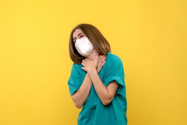 Vooraanzicht vrouwelijke arts met keelpijn op gele ruimte