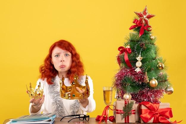 Vooraanzicht vrouwelijke arts met kronen rond kerstboom en cadeautjes