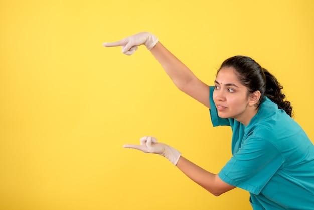 Vooraanzicht vrouwelijke arts met latexhandschoenen die met linker vinger wijzen