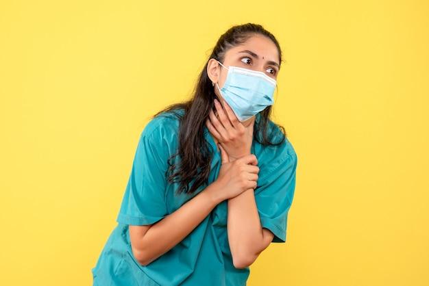 Vooraanzicht vrouwelijke arts met masker dat haar keel staande houdt
