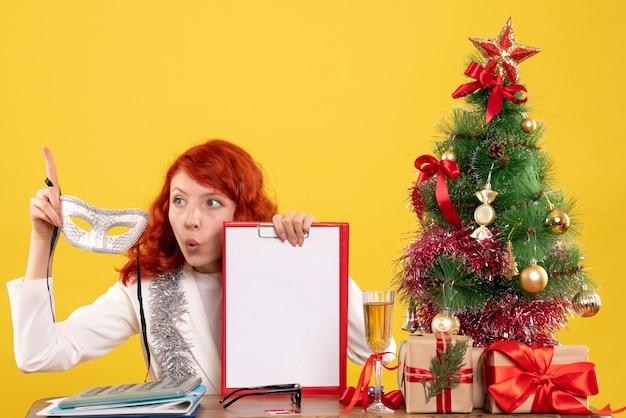 Vooraanzicht vrouwelijke arts met masker en dossiernota rond kerstboom