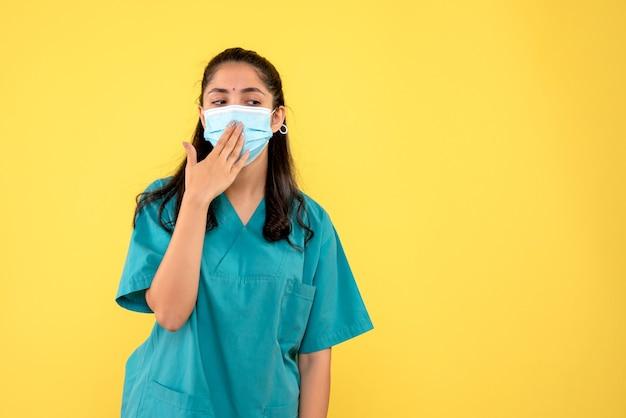 Vooraanzicht vrouwelijke arts met masker hand aan haar mond brengen