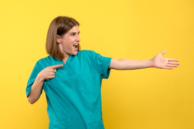 Vooraanzicht vrouwelijke arts met opgewonden uitdrukking op gele ruimte