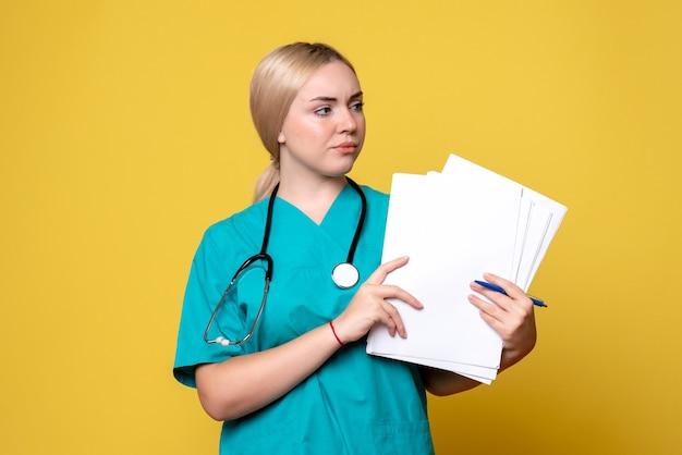 Vooraanzicht vrouwelijke arts met papieren, coronavirus gezondheid medic virus covid verpleegster ziekenhuis