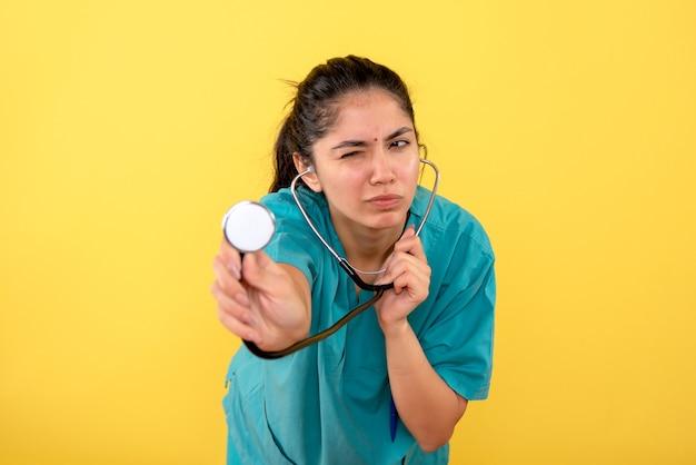 Vooraanzicht vrouwelijke arts met stethoscoop in haar hand staan