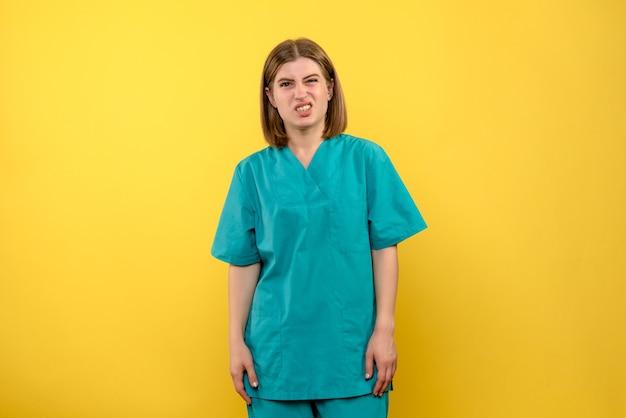 Vooraanzicht vrouwelijke arts met verwarde uitdrukking op gele ruimte