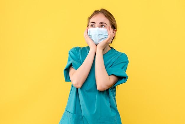 Vooraanzicht vrouwelijke arts opgewonden op gele achtergrond ziekenhuis gezondheid covid-pandemie