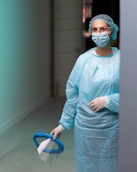 Vooraanzicht vrouwelijke arts pandemische apparatuur dragen