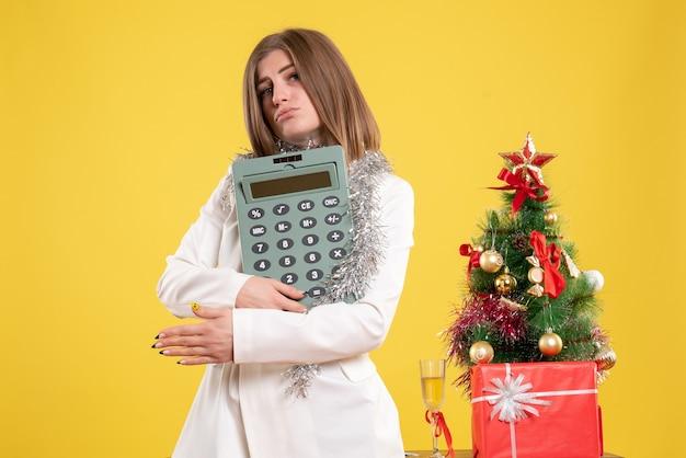 Vooraanzicht vrouwelijke arts permanent en houdt rekenmachine op gele achtergrond met kerstboom en geschenkdozen