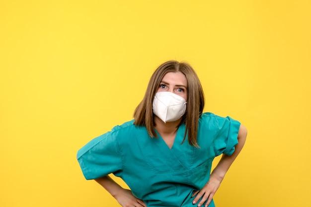 Vooraanzicht vrouwelijke arts poseren met masker op gele ruimte