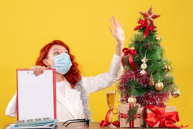 Vooraanzicht vrouwelijke arts rond kerstboom en cadeautjes zitten in masker