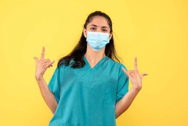 Vooraanzicht vrouwelijke arts rotsteken met beide handen maken