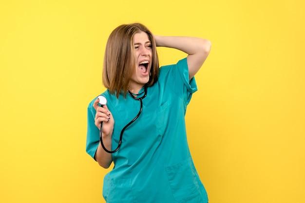Vooraanzicht vrouwelijke arts tonometer op gele ruimte te houden