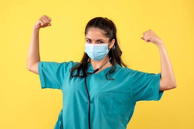 Vooraanzicht vrouwelijke arts toont haar kracht staan